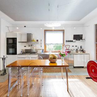 Immagine di una grande sala da pranzo aperta verso la cucina boho chic con pareti bianche, parquet chiaro e camino lineare Ribbon
