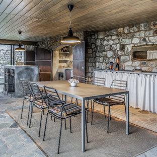 Idee per una sala da pranzo aperta verso la cucina mediterranea con nessun camino e pavimento grigio