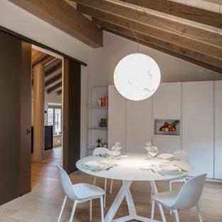 Foto di una sala da pranzo aperta verso la cucina minimal di medie dimensioni con pareti bianche, parquet chiaro e pavimento beige