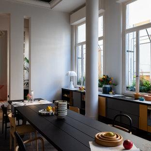 Foto di una sala da pranzo aperta verso la cucina contemporanea con pareti grigie, pavimento in legno massello medio e pavimento marrone