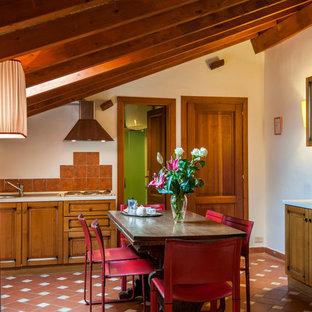 Idées déco pour une salle à manger ouverte sur la cuisine campagne avec un mur blanc, un sol en carreau de terre cuite et un sol rouge.