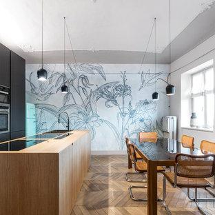 Immagine di una sala da pranzo aperta verso la cucina minimal con pareti grigie, pavimento in legno massello medio e pavimento marrone