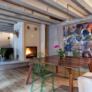 Immagine di una sala da pranzo aperta verso il soggiorno industriale di medie dimensioni con camino bifacciale, cornice del camino in intonaco e parquet chiaro