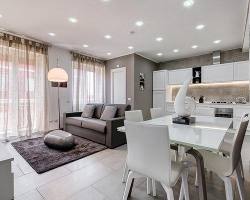 Sala da pranzo aperta verso il soggiorno con pavimento con ...