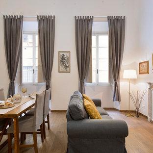 Foto di una sala da pranzo design con pareti bianche, pavimento in legno massello medio, camino classico e pavimento marrone