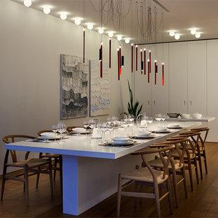Exemple d'une salle à manger tendance fermée avec un mur blanc et un sol en bois brun.