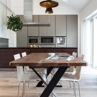 Immagine di una grande sala da pranzo aperta verso la cucina moderna con pavimento in legno massello medio