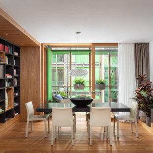 Immagine di una sala da pranzo design con pavimento in legno massello medio, pareti bianche e nessun camino