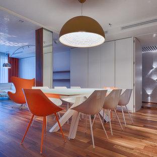 Immagine di una sala da pranzo design con pareti bianche, parquet scuro, camino ad angolo e cornice del camino in intonaco
