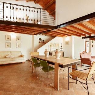 Imagen de comedor mediterráneo, grande, abierto, con paredes blancas, suelo de baldosas de terracota y suelo rosa