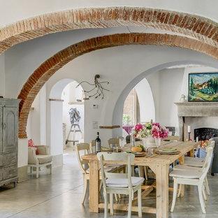 Foto di una grande sala da pranzo mediterranea con pareti bianche e pavimento in cemento
