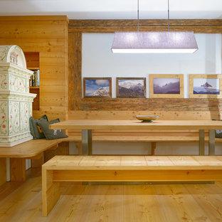 Immagine di una piccola sala da pranzo aperta verso il soggiorno in montagna con pareti marroni, parquet chiaro, stufa a legna, cornice del camino piastrellata e pavimento marrone