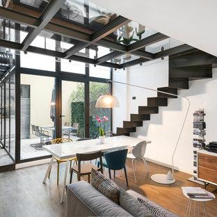 Esempio di una piccola sala da pranzo aperta verso il soggiorno design con pareti bianche, pavimento in legno massello medio e pavimento marrone