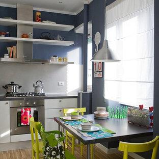 Immagine di una sala da pranzo aperta verso la cucina design con pareti blu, parquet chiaro e pavimento beige