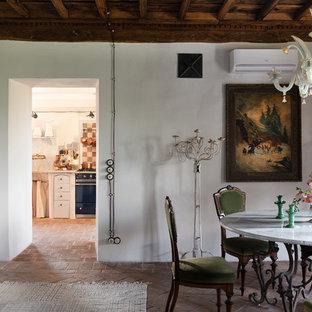 Idee per una sala da pranzo bohémian con pareti bianche e pavimento in mattoni