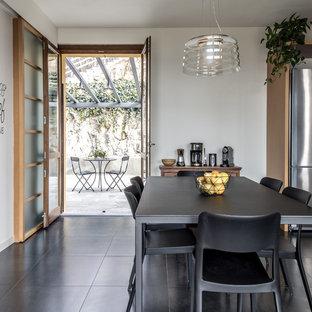 Ispirazione per una sala da pranzo aperta verso la cucina tradizionale di medie dimensioni con pareti bianche, pavimento in gres porcellanato e pavimento nero