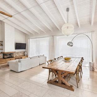 Immagine di una sala da pranzo aperta verso il soggiorno country con pareti bianche, camino lineare Ribbon e pavimento beige