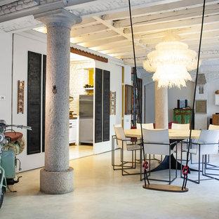 Immagine di una grande sala da pranzo industriale con pareti bianche e pavimento in gres porcellanato