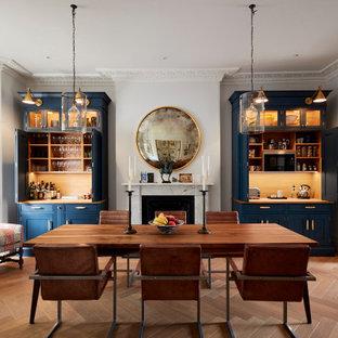 Ispirazione per una sala da pranzo tradizionale chiusa con pareti grigie, pavimento in legno massello medio, camino classico e pavimento marrone