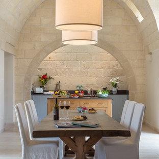 Esempio di una sala da pranzo aperta verso la cucina mediterranea con pareti beige e pavimento grigio