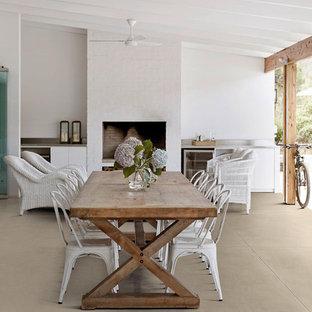 Ispirazione per una sala da pranzo marinara con pavimento in gres porcellanato, pareti bianche, camino classico e pavimento beige