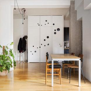 Idee per una sala da pranzo aperta verso il soggiorno minimal con pareti bianche, nessun camino e parquet chiaro