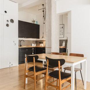 Immagine di una piccola sala da pranzo aperta verso la cucina design con pareti bianche, parquet chiaro e nessun camino