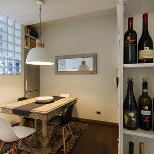 Bild på en mellanstor funkis matplats med öppen planlösning, med vita väggar, ljust trägolv, en öppen hörnspis och en spiselkrans i trä