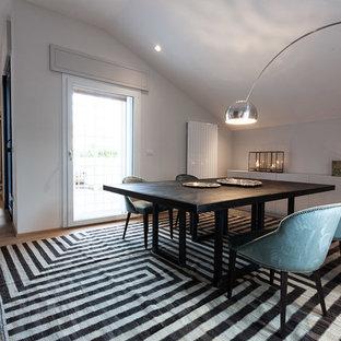 Immagine di una sala da pranzo aperta verso il soggiorno minimal con pareti bianche e parquet chiaro