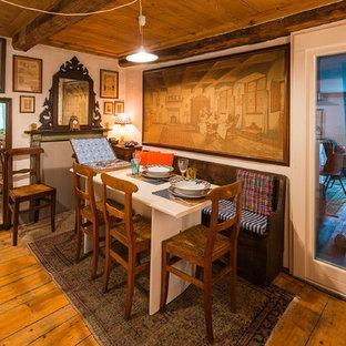 Cette image montre une salle à manger rustique avec un mur blanc et un sol en bois brun.