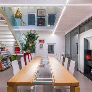 Esempio di una sala da pranzo contemporanea con pareti bianche, camino classico e pavimento grigio