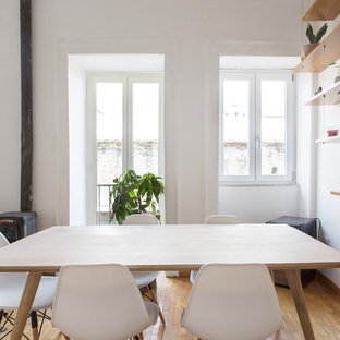 Foto di una sala da pranzo aperta verso il soggiorno scandinava con pareti bianche, pavimento in legno massello medio, stufa a legna e pavimento marrone