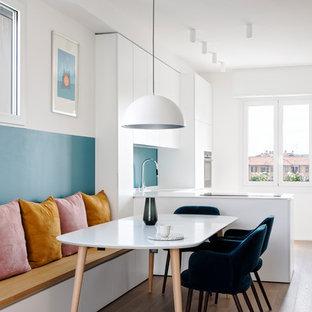 Immagine di una sala da pranzo aperta verso la cucina contemporanea di medie dimensioni con pavimento in legno massello medio, pareti bianche e pavimento marrone