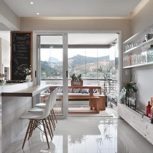 Ispirazione per una sala da pranzo moderna di medie dimensioni con pareti beige, pavimento in gres porcellanato, camino sospeso, cornice del camino in pietra e pavimento beige
