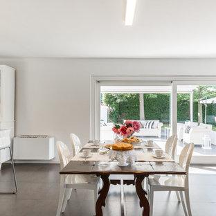 Immagine di una sala da pranzo aperta verso il soggiorno bohémian di medie dimensioni con pareti bianche, nessun camino e pavimento nero