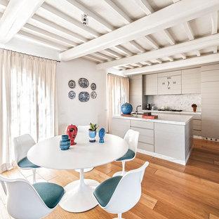 Immagine di una sala da pranzo aperta verso la cucina mediterranea con pavimento in legno massello medio e pareti bianche