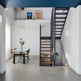 Idee per una grande sala da pranzo aperta verso il soggiorno design con pareti bianche, camino bifacciale, cornice del camino piastrellata, pavimento grigio e pavimento in gres porcellanato