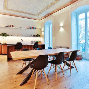 Immagine di una grande sala da pranzo aperta verso la cucina design con pareti bianche, pavimento in legno massello medio e pavimento marrone