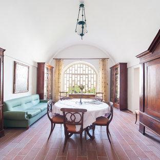 Aménagement d'une salle à manger ouverte sur le salon méditerranéenne avec un mur blanc, un sol en carreau de terre cuite, aucune cheminée et un sol rouge.