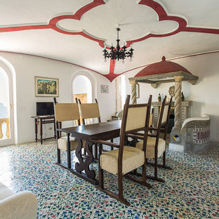Immagine di una sala da pranzo mediterranea chiusa con pareti bianche, pavimento con piastrelle in ceramica, camino classico e cornice del camino in pietra
