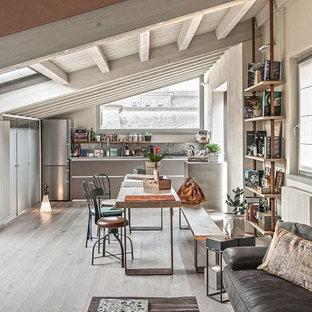 Esempio di una sala da pranzo aperta verso il soggiorno industriale con pareti beige, parquet chiaro e pavimento grigio