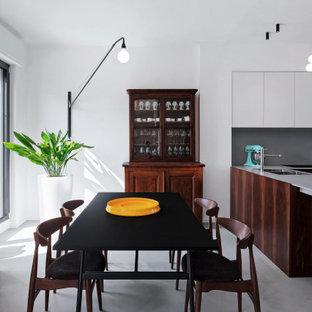 Foto di una grande sala da pranzo aperta verso la cucina contemporanea con pareti bianche, pavimento in cemento e pavimento grigio