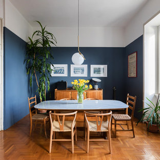 Cette image montre une salle à manger nordique fermée avec un mur bleu, un sol en bois brun et un sol orange.