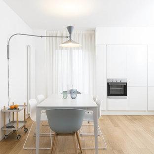 Ispirazione per una sala da pranzo aperta verso la cucina nordica con pareti bianche, parquet chiaro e pavimento beige
