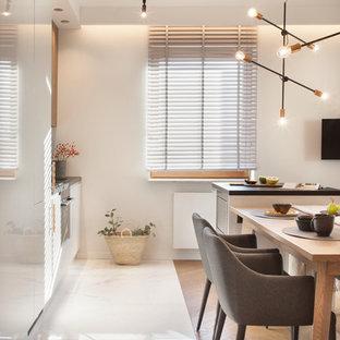 Ispirazione per una sala da pranzo aperta verso la cucina moderna di medie dimensioni con pareti bianche, pavimento in gres porcellanato e pavimento bianco