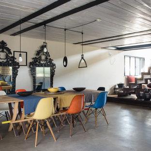 Exemple d'une salle à manger ouverte sur le salon industrielle avec cheminée suspendue.