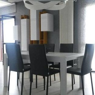 Immagine di una piccola sala da pranzo aperta verso il soggiorno moderna con pareti grigie, pavimento in gres porcellanato, camino lineare Ribbon, cornice del camino in cemento e pavimento grigio