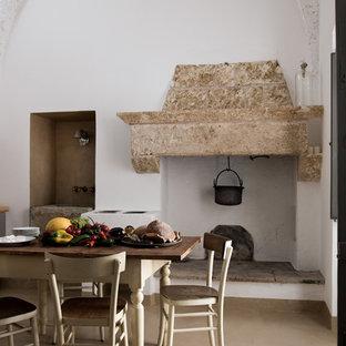 Ejemplo de comedor de cocina de estilo de casa de campo con paredes blancas, suelo de baldosas de porcelana, chimenea tradicional y marco de chimenea de piedra