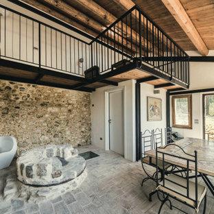 Foto di una grande sala da pranzo mediterranea con pareti bianche, pavimento in mattoni e pavimento grigio