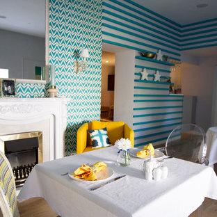 Diseño de comedor de cocina bohemio, de tamaño medio, con suelo de madera en tonos medios, chimenea tradicional, paredes multicolor, marco de chimenea de madera y suelo amarillo